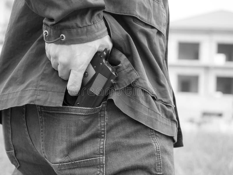 Mężczyzna, policjant lub rabuś, gangster kryje jego pistolet za jego z powrotem obraz stock