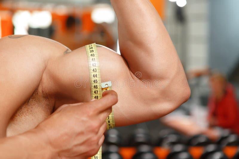 Mężczyzna pomiarowy rozmiar jego bicepsy zdjęcia royalty free