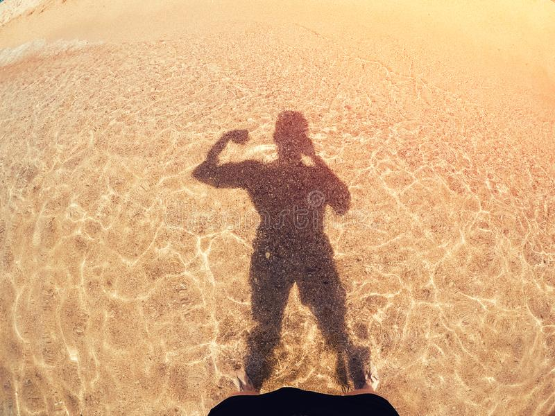 Mężczyzna pompujący w górę mięśni robi selfie sylwetki cieniom od słońca na złotym piasku i morzu Pojęcia przygotowanie dla lata obraz stock