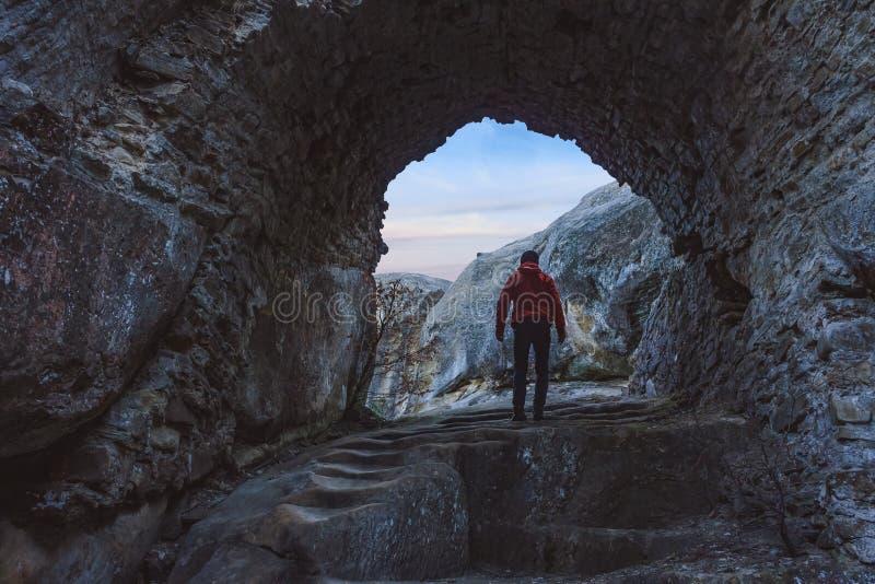 Mężczyzna postać iść przez kamiennego łuku w wschód słońca fotografia royalty free