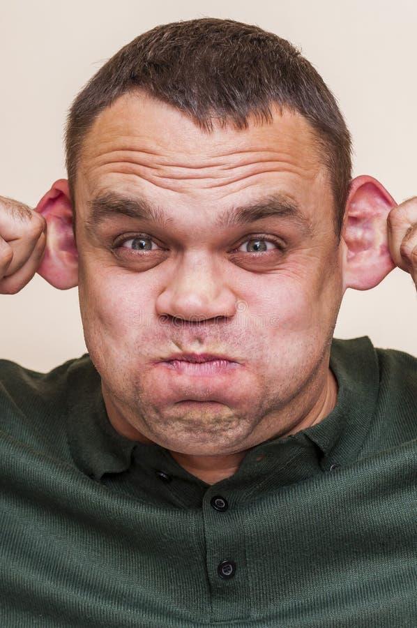 Mężczyzna pouting usta, ciągnąć na boku ucho i Pokazywać małpy fotografia royalty free
