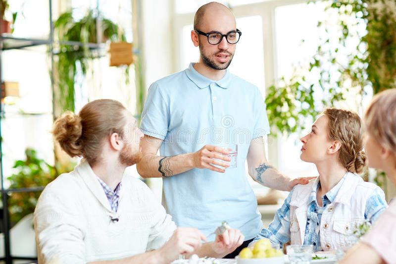 Mężczyzna pozycja i mówić przyjaciele grzanka obraz stock