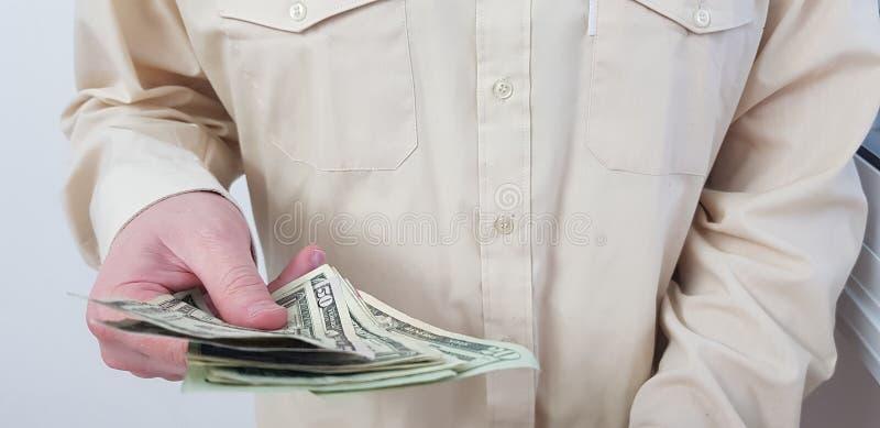 Mężczyzna pozycja jest ubranym lekkich barwionych oficjalnych koszula chwyty w jego wręcza amerykańskiego dolara fotografia royalty free