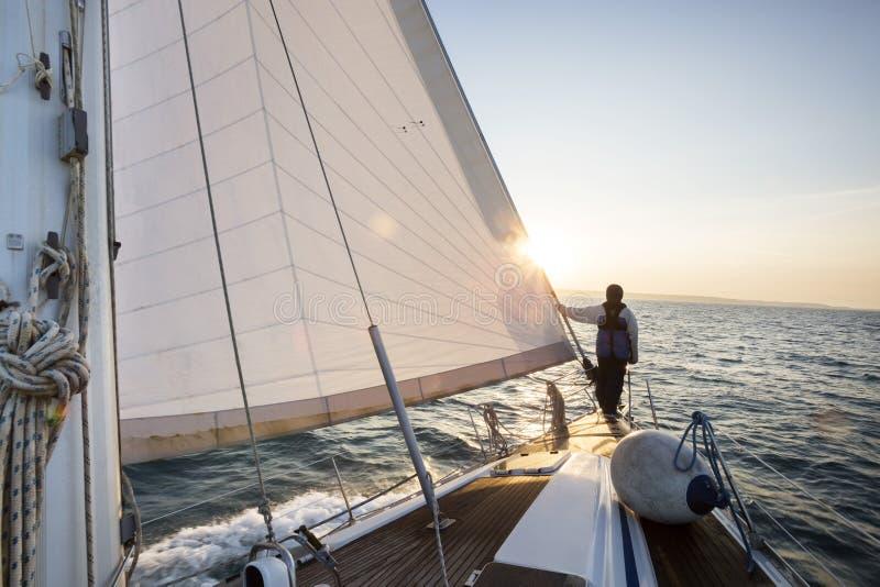 Mężczyzna pozycja Na przodzie żagiel łódź W morzu zdjęcie royalty free