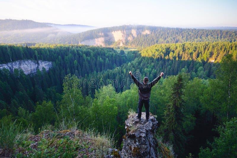 Mężczyzna pozycja na wierzchołku góra z nastroszonymi rękami obraz royalty free