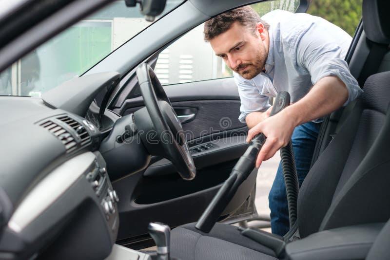 Mężczyzna próżnia czyści jego samochód obraz stock