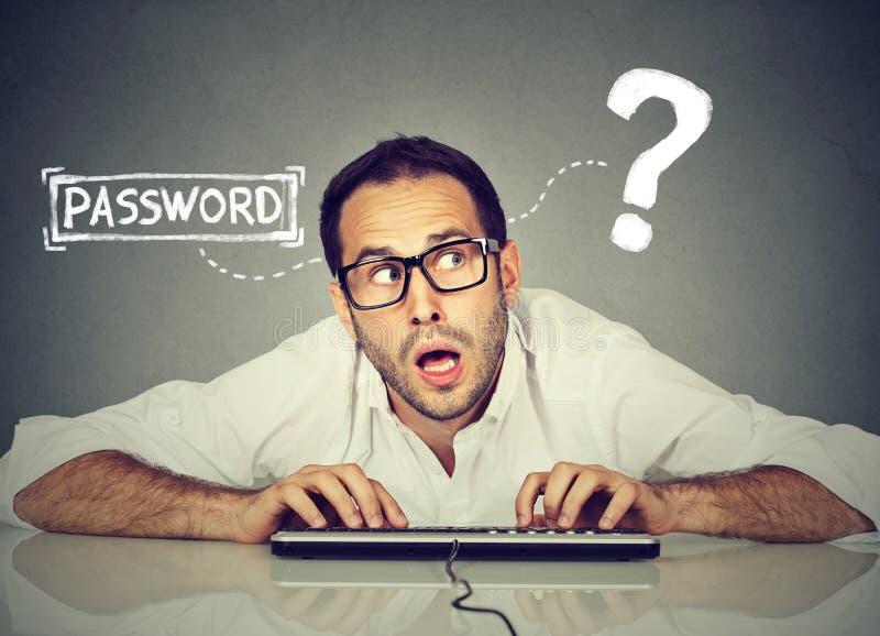 Mężczyzna próbuje notować w jego komputer zapominał hasło zdjęcia stock