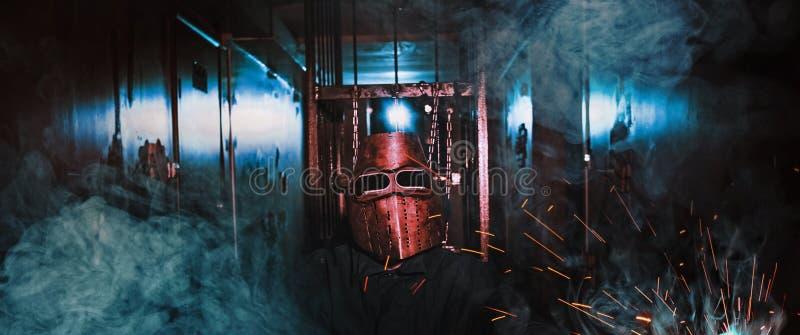 Mężczyzna pracownika maski iskry dymią ciemnego pokój zdjęcia royalty free