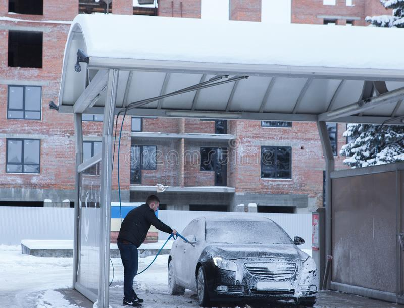 Mężczyzna pracownika ` s płuczkowy samochodowy aliaż toczy na samochodowym obmyciu Pojęcie samochodowy obmycie zdjęcia royalty free