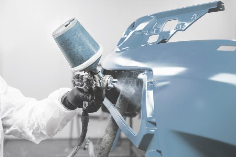Mężczyzna pracujący w ubraniach ochronnych i maskach malujących zderzak samochodowy za pomocą farby natryskowej obrazy stock