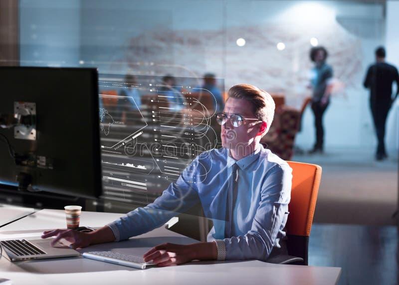 Mężczyzna pracuje na komputerze w ciemnym biurze zdjęcia royalty free