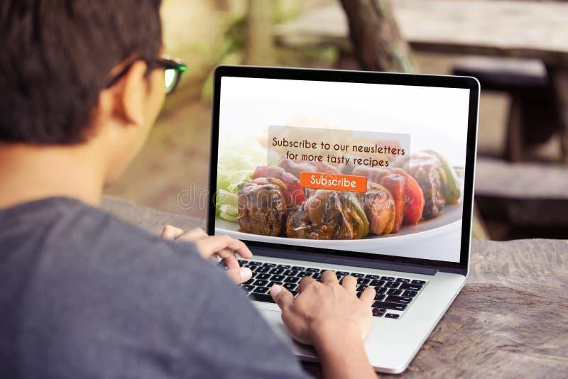 Mężczyzna pracuje na laptopie, komputerowym robić/prenumeruje karmowego blog na ekranie zdjęcia royalty free
