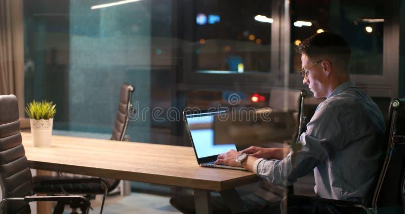 Mężczyzna pracuje na laptopie w ciemnym biurze zdjęcie stock