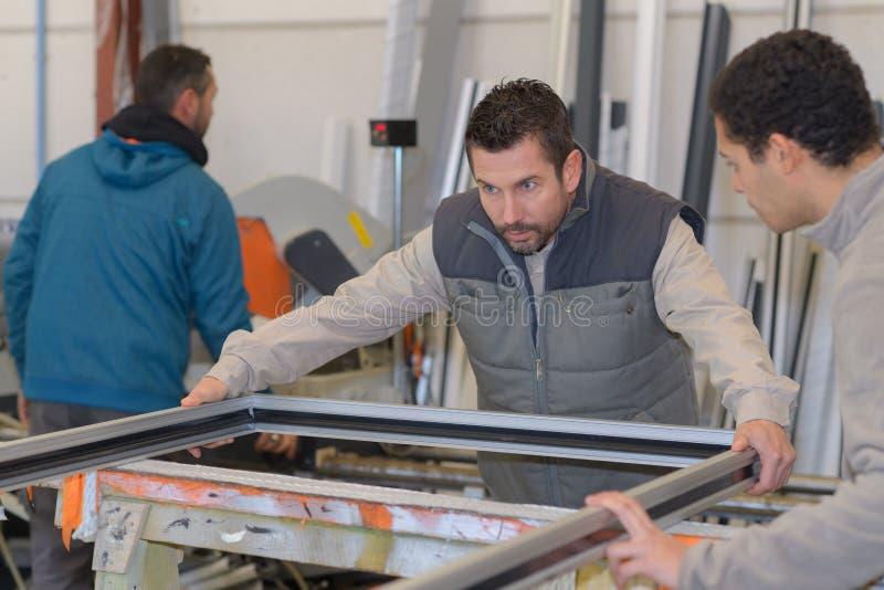 Mężczyzna pracuje przy plastikowym drzwi i okno fabryką zdjęcia stock