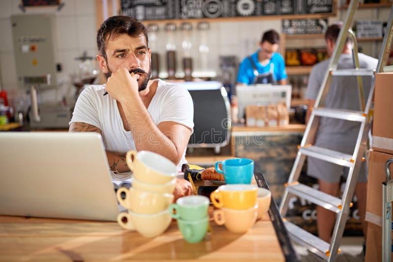 Mężczyzna pracuje przy sklepem z kawą - sklepu z kawą właściciel obrazy stock