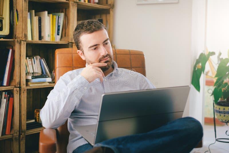 Mężczyzna pracuje w domu używać jego laptop obrazy royalty free