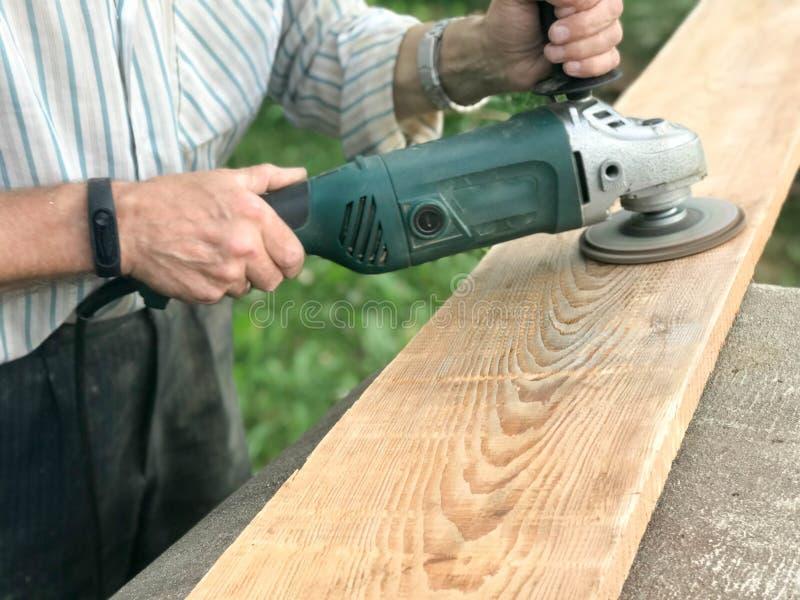 Mężczyzna pracuje z jego rękami, mleje dyska wokoło dla ostrzarza elektryczny narzędzie dla mleć powierzchnię i polerować obrazy stock