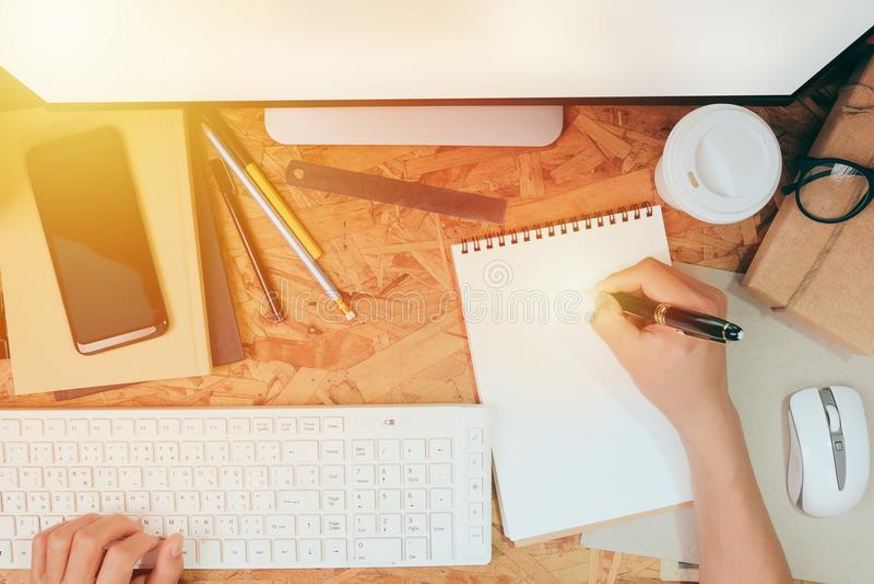 Mężczyzna pracuje z komputerową pisać na maszynie klawiaturą i pisze piórze na notatniku, odgórnego widoku ministerstwo spraw wew obrazy royalty free