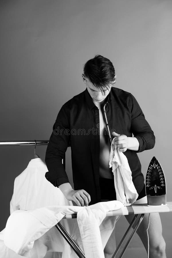 Mężczyzna prasowanie odziewa z żelazem na pokładzie obraz royalty free