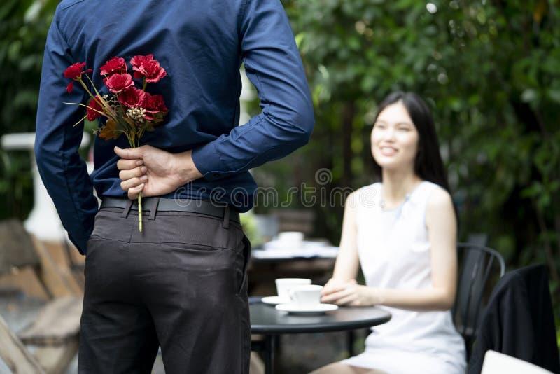 Mężczyzna proponuje małżeństwo z uśmiechniętą kobietą z pięknym bukietem w pięknym ogrodzie obrazy stock