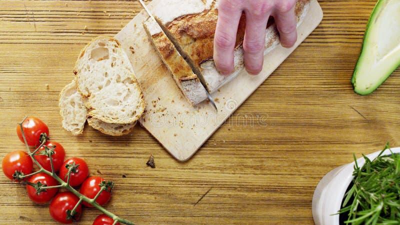 Mężczyzna przecinania bochenki chleb obraz stock