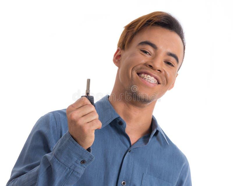 Mężczyzna przedstawia samochodowego klucz Czarny młody człowiek jest ubranym błękitnego ogólnospołecznego shir obraz royalty free