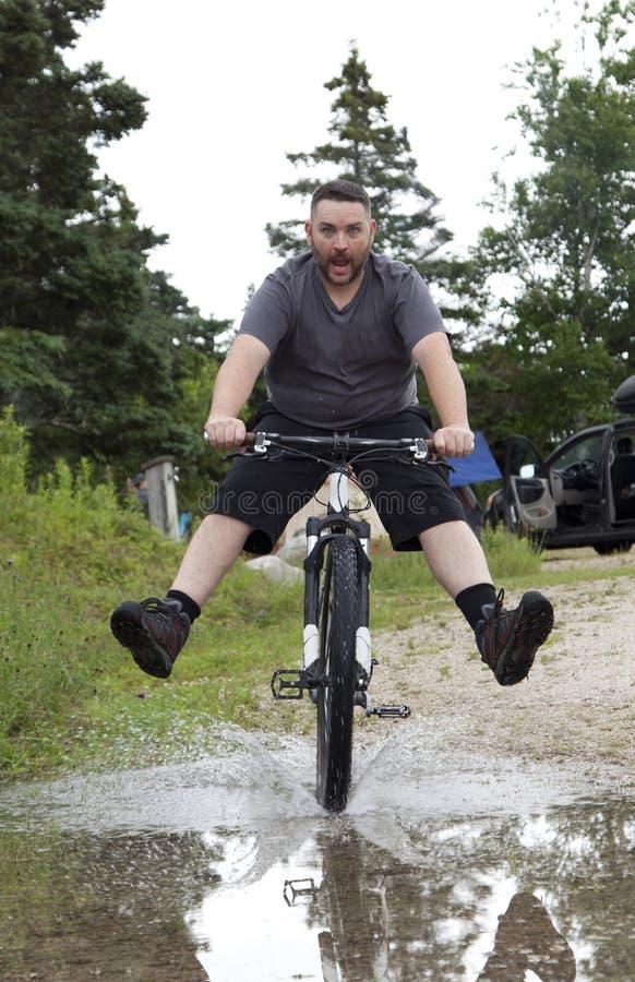 Mężczyzna przejażdżek rower przez kałuży/ zdjęcie royalty free
