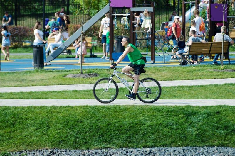 Mężczyzna przejażdżki bicykl w Butovo parku, Moskwa, Rosja zdjęcia stock