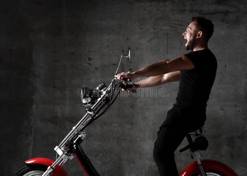 Mężczyzna przejażdżki elektrycznego samochodu nowego motocyklu rowerowa hulajnoga w czarny sukiennym krzyczy za głośnym na betono obrazy royalty free