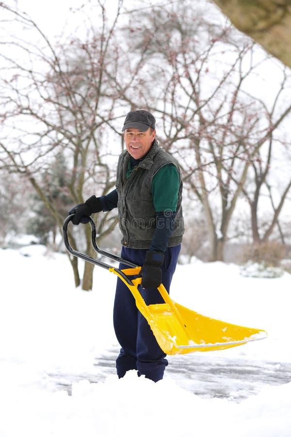 Mężczyzna przeszuflowywa śnieżny ono uśmiecha się obrazy royalty free
