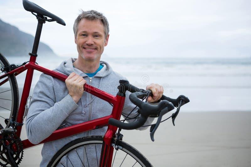Mężczyzna przewożenia bicykl na plaży zdjęcia stock