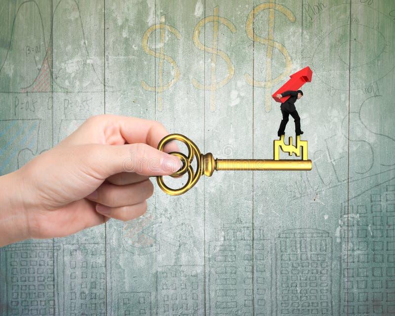 Mężczyzna przewożenia strzała w górę równoważenia na kluczu w funta znaku zdjęcie stock