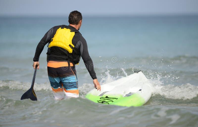 Mężczyzna przewodzi out w oceanu weari z paddleboard i paddle zdjęcia stock