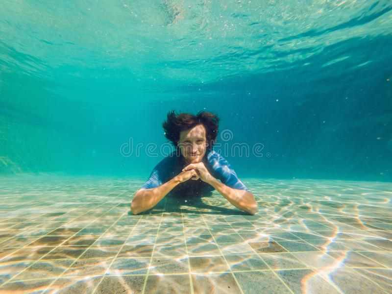 Mężczyzna przy dnem basen, nurkuje pod wodą fotografia stock