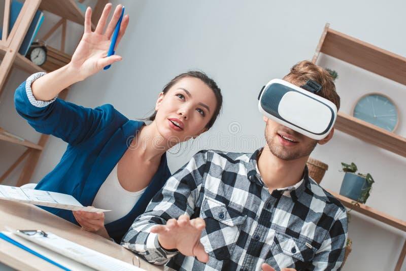 Mężczyzna przy nieruchomości agencji obsiadaniem w rzeczywistości wirtualnej słuchawki klienta faktorskiej promuje usłudze obrazy stock