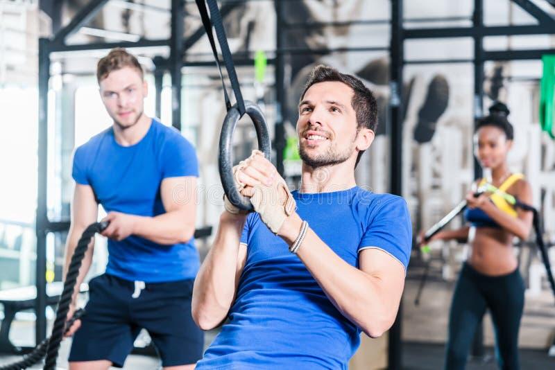 Mężczyzna przy pierścionkami robi sprawności fizycznej ćwiczeniu w gym obraz royalty free