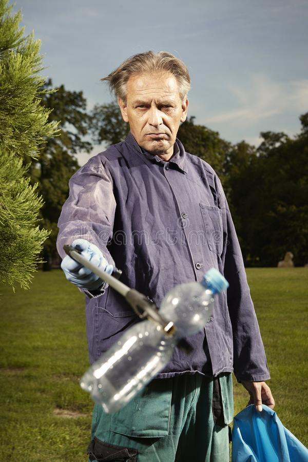 Mężczyzna przy pracą podnosi w górę śmieci na trawie w parku zdjęcia royalty free