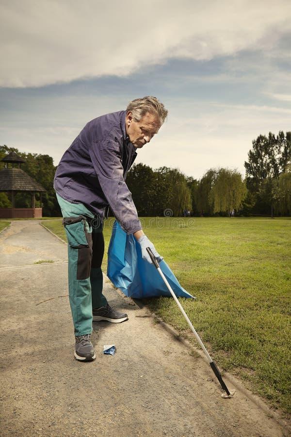 Mężczyzna przy pracą podnosi w górę śmieci na trawie w parku zdjęcie royalty free