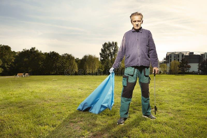 Mężczyzna przy pracą podnosi w górę śmieci na trawie w parku obrazy royalty free