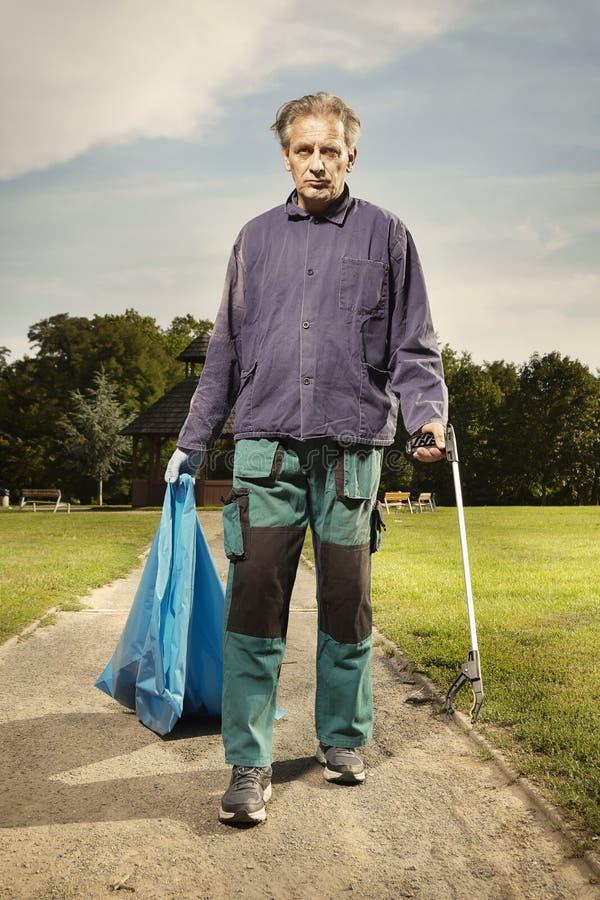 Mężczyzna przy pracą podnosi w górę śmieci na trawie w parku fotografia royalty free