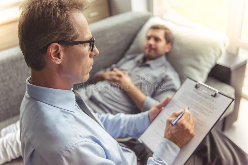 Mężczyzna przy psychoterapeuta zdjęcie stock