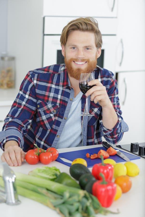 Mężczyzna przygotowujący obiad w kuchni podczas zabawy w wino zdjęcia royalty free
