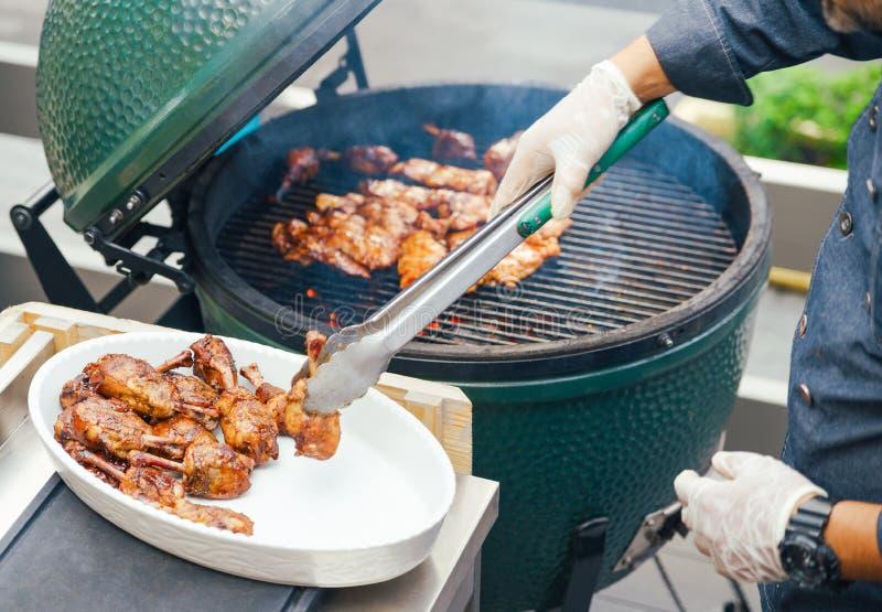 Mężczyzna przygotowywa kurczaka mięso z piec na grillu asparagusem dla gości, przyjaciele Łomotać pojęcie odżywianie bufet Jedzen obraz royalty free