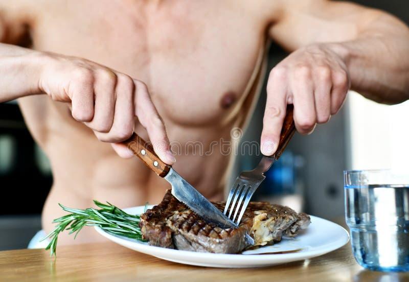 Mężczyzna przygotowywający jeść cięcie z rozwidleniem, nożowym grill wołowiny stek i szkło woda na kuchni fotografia stock