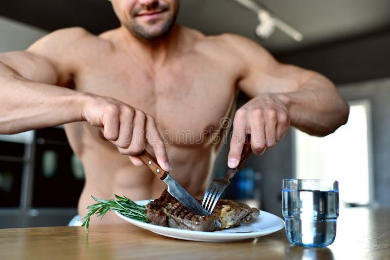 Mężczyzna przygotowywający jeść cięcie z rozwidleniem, nożowym grill wołowiny stek i szkło woda na kuchni fotografia royalty free