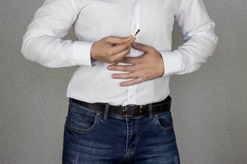 Mężczyzna przylega jego żołądek, żołądek w którym płonąca furora, zgaga, dopasowanie i pożarniczy oparzenie przeciw brzuchowi, obrazy stock