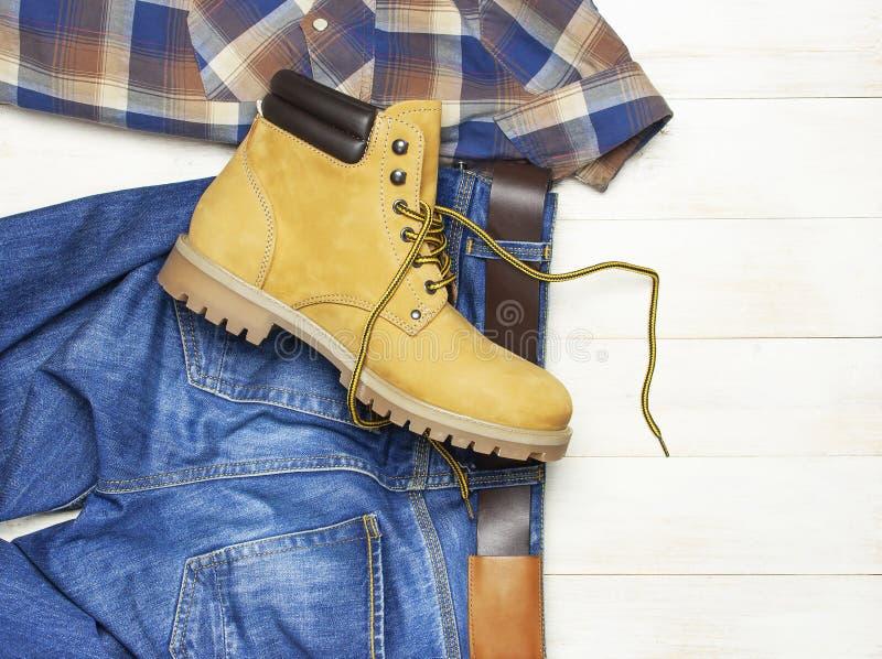 Mężczyzna przypadkowa odzież, żółta praca inicjuje od naturalnej nubuck skóry, niebieskich dżinsów, w kratkę koszula i brązu pask zdjęcie royalty free