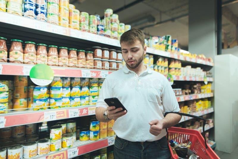 Mężczyzna przystojni spojrzenia przy listą zakupów na jego telefonie gdy robiący zakupy przy supermarketem obraz stock