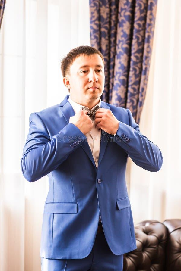 Mężczyzna przystosowywa jego łęku krawat w błękitnym kostiumu podczas gdy stojący przeciw lustru obraz royalty free