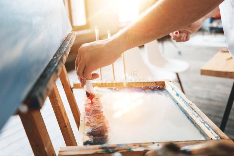 Mężczyzna ręka gniesie farbę od tubki na palecie artysty zbliżenie Malarz mieszanek nafciana farba barwi na palecie w warsztacie fotografia royalty free
